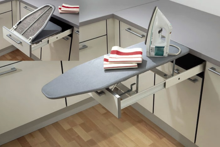 Retractable ironing board under the working surface of the kitchen cabinet.