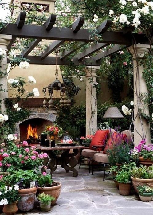 Прекрасная идея дизайна перголы с каменными колоннами и деревянной крышей, в окружении цветов, лиан, зелени.