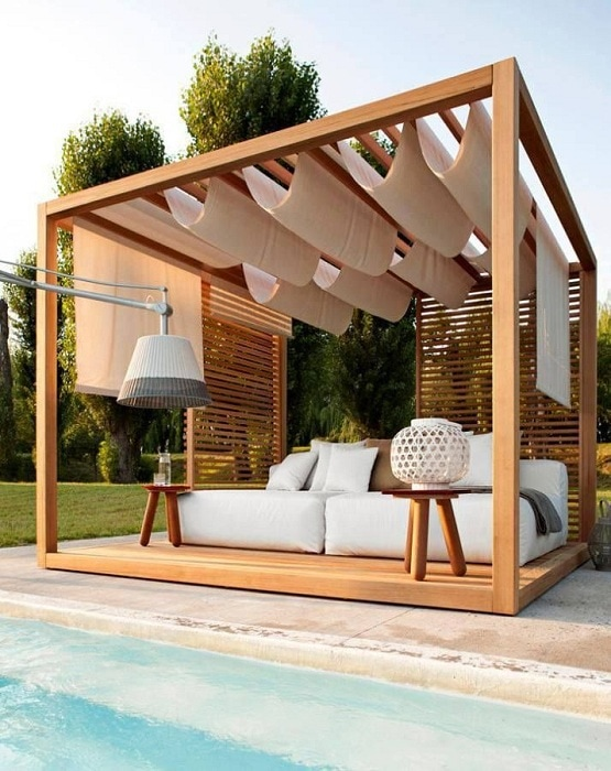 A simple wooden arbor under which the bed by the pool is hidden.