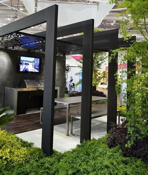 A minimalist metal pergola with clear lines surrounded by greenery.