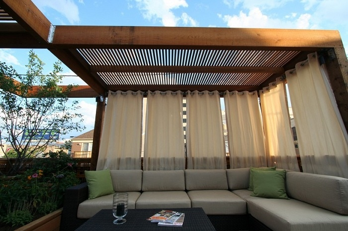 A simple but pretty pergola is decorated with cute curtains that create an incredibly comfortable atmosphere.