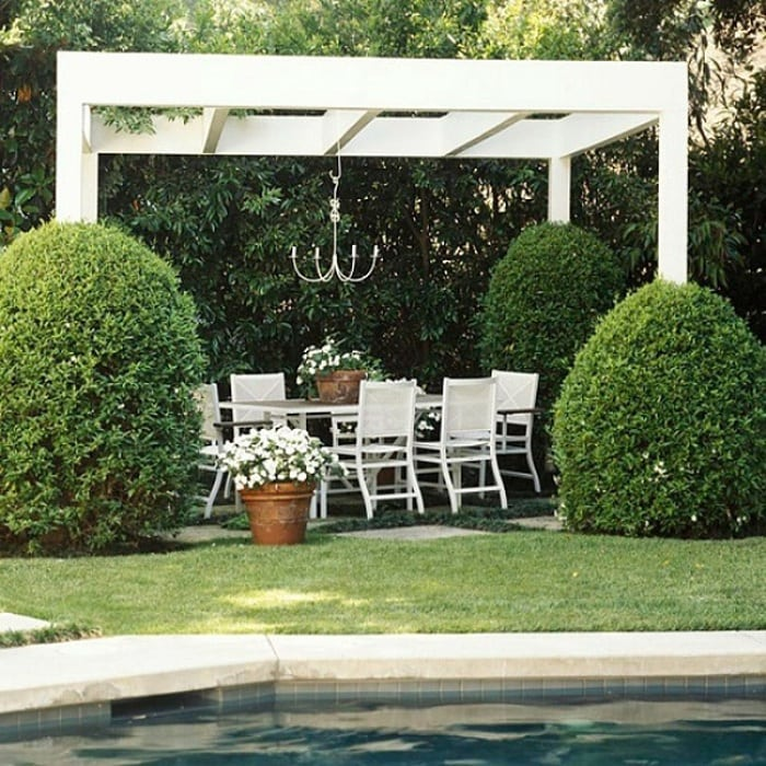 White vinyl arbor with a lounge by the pool, which protects and emphasizes the greenery around.