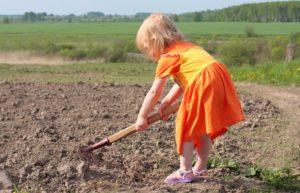 девочка работает тяпкой на даче