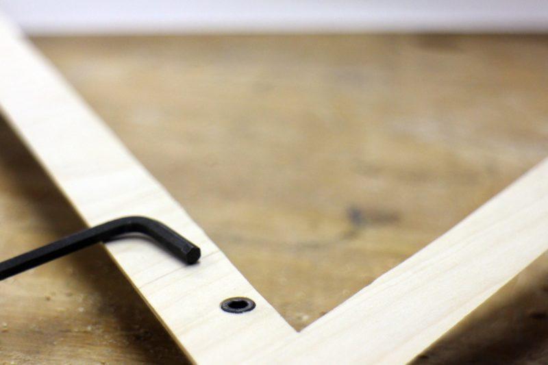 винт вкрученный в деревянную раму